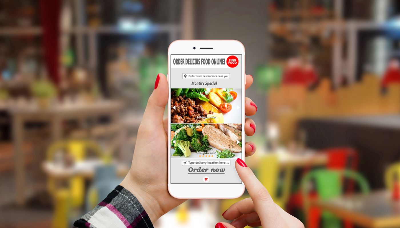 Close up view of hands holding smartphone, index finger pressing online order button with restaurant landscape in background.