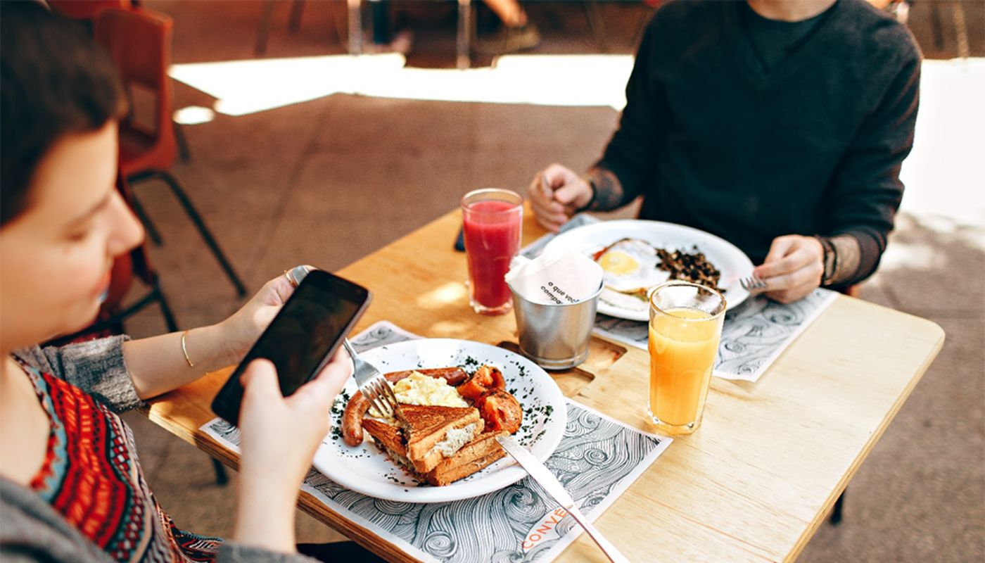 3/4 close up of woman looking at smartphone seated at tan square table with orange juice and white plate with French toast.