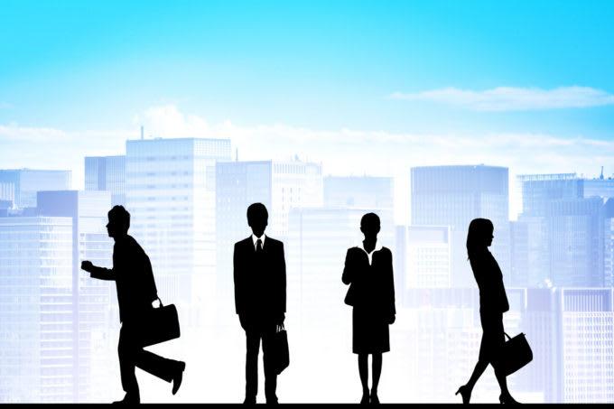 ビル群の絵の前のビジネススーツを着た男女4人のシルエット