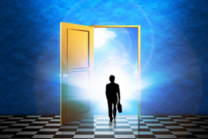 未来へのドアを開けてその中に消えていくイメージの人