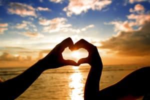 水平線の夕日に向けてハートを指で作る二人