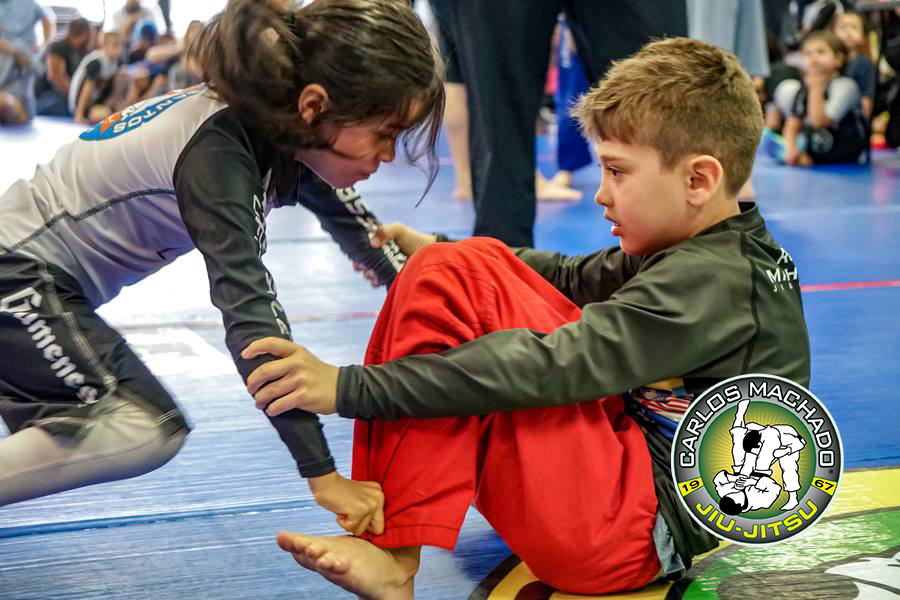 Two jiu jitsu kids, a boy versus a girl during an in-house tournament