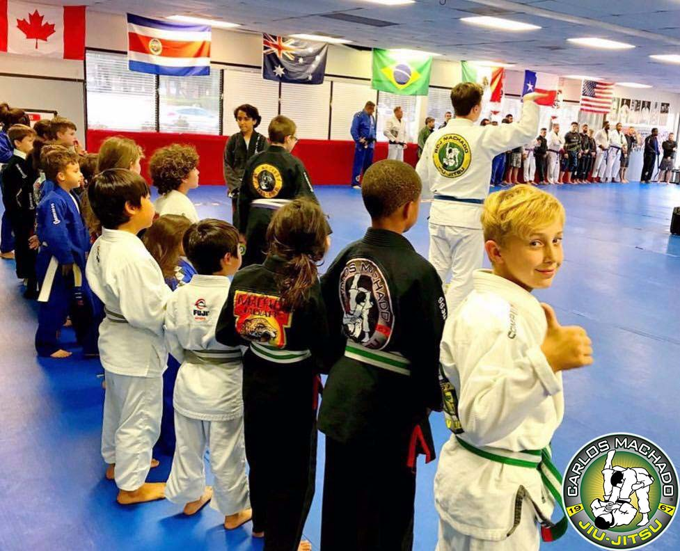 A group of jiu jitsu kids displaying attention and focus during class while one student poses for a photo.