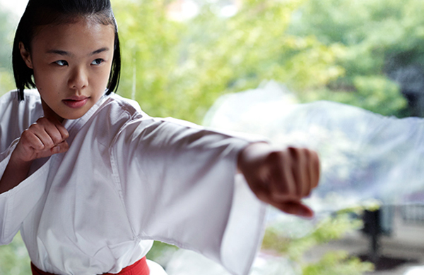 karate girl in a gee punching