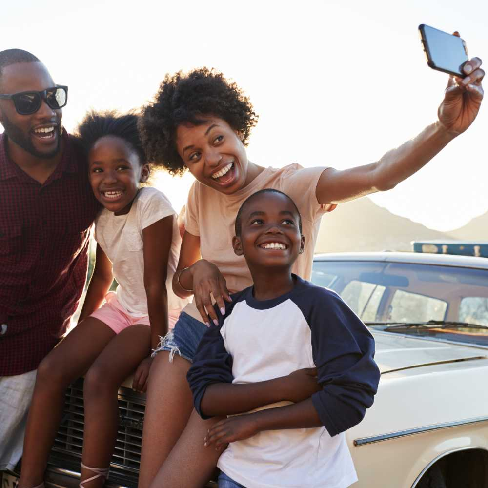 Family of four taking a selfie while sitting on the hood of car