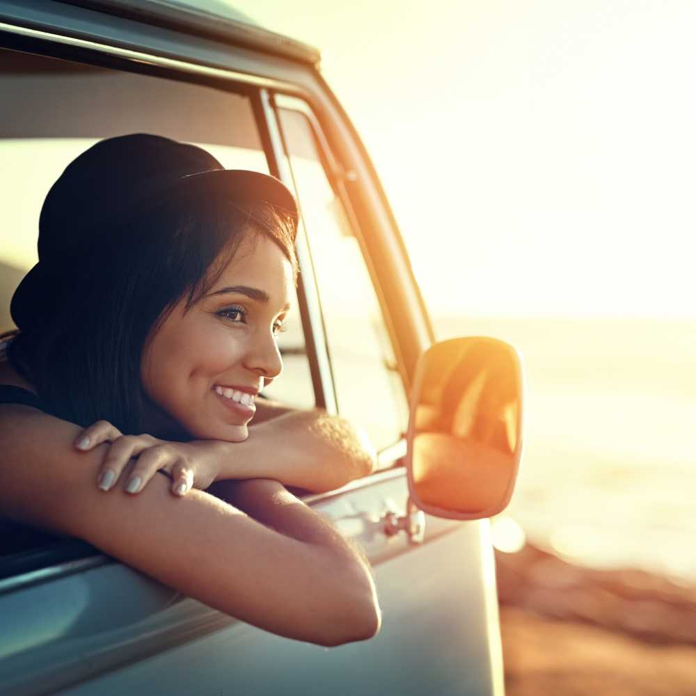Woman in a car smiling with her chin rested on her folded arms upon the car door frame