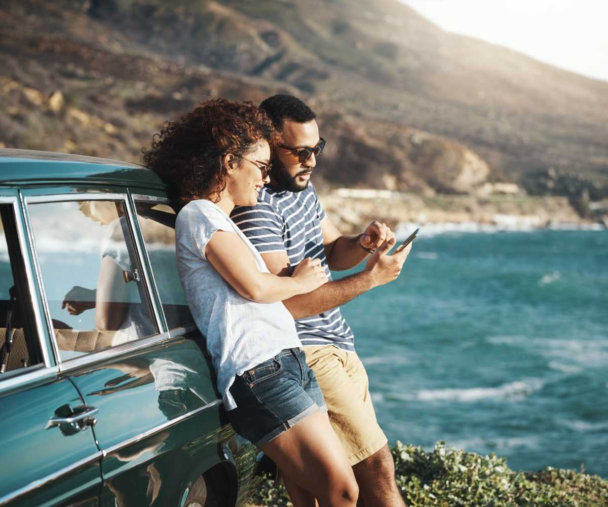 Couple looking at a phone leaning against a car aside the ocean