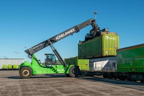 En grön containerkran lyfter upp en last.