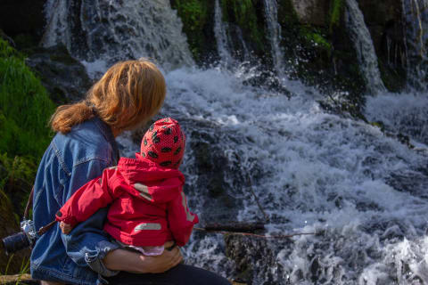 En kvinna och ett barn är fotograferade bakifrån. De tittar på ett vattenfall. Barnet sitter i kvinnans knä.