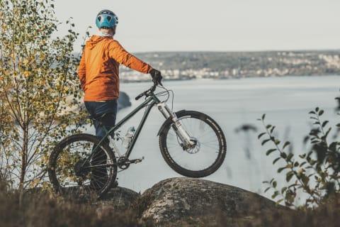 En man står och håller i sin cykel. Han är fotograferad bakifrån och tittar rakt fram. Framför mannen syns Vättern, samt delar av Huskvarna och Jönköping. Solen skiner och vattnet är ljusblått.