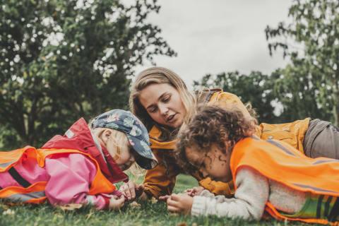 Två förskolebarn och en pedagog ligger i gräset och tittar på insekter. Det är höst och barnen har på sig orangea västar.