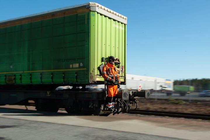 En man står på baksidan av en lastbil som är i rörelse. Mannen och lastbilen är fotograferade snett framifrån.