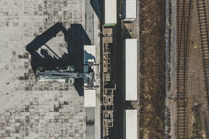 En containerkran lyfter upp en last. Scenen är fotograferad ovanifrån.