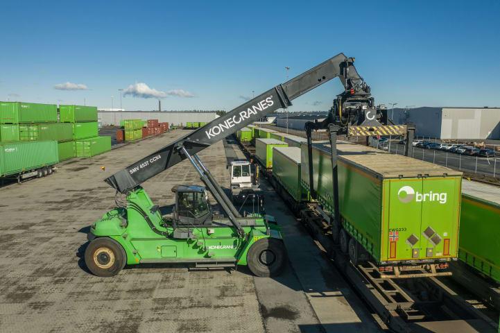 En grön containerkran lyfter upp en last. Scenen är fotograferad från sidan.
