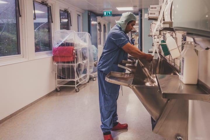 En man är fotograferad från sidan i en upplyst sjukhuskorridor. Han tvättar sina händer och är iklädd blå sjukhuskläder.