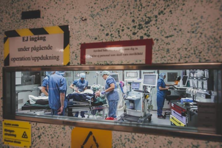 Fem personer iklädda operationskläder befinner sig i ett operationsrum. Fyra av dem står samlade omkring en patient som ligger på en operationsbrits. Den femte personen står i ett hörn och skriver på en dator.