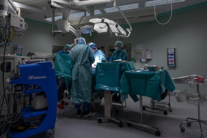 Fyra läkare i operationskläder står omkring en patient som ligger på en operationsbrits. På ett bord bredvid dem ligger medicinska verktyg.