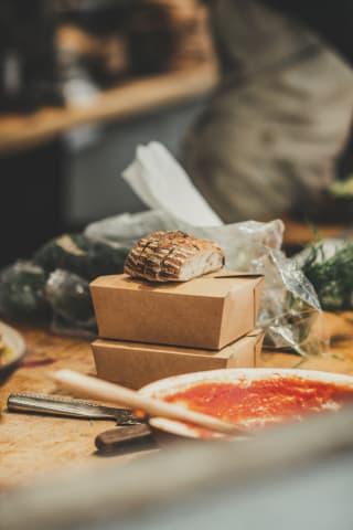 Två lunchlådor i pappförpackning och några brödskivor är i fokus. Framför lådorna finns en tallrik med tomtatsås.