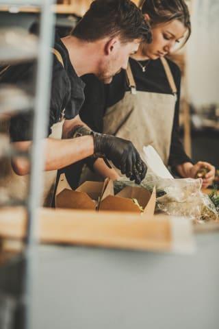 En kvinna och en man står i restaurangköket och fyller upp två matlådor i pappförpackning. De är fotograferade från sidan och tittar ner på arbetsbänken.