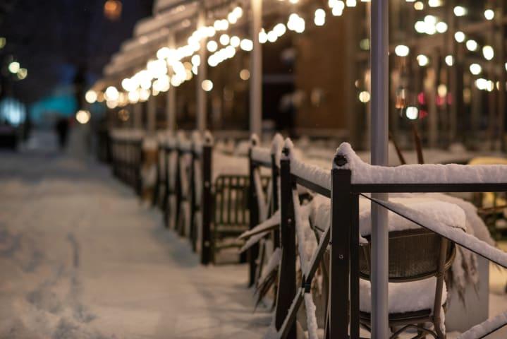 En uteservering är full av snö. Det är mörkt ute och platsen är upplyst av lampor.