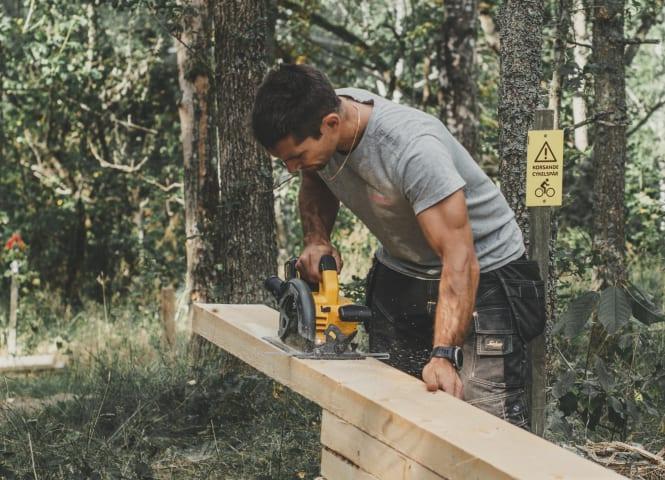 En man håller på att kapa en bräda med en cirkelsåg. Han står utomhus och är omgiven av träd. Mannen är fotograferad från sidan, och tittar ner på brädan. Han har på sig en grå t-shirt och svarta snickarbyxor.