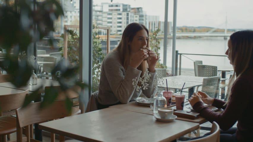 Två kvinnor sitter vid ett bort på ett café. De tittar på varandra och den ena kvinnan håller en macka nära munnen.