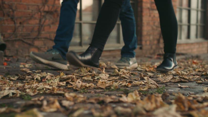 En man och en kvinna går på en kullerstensgata full av löv.
