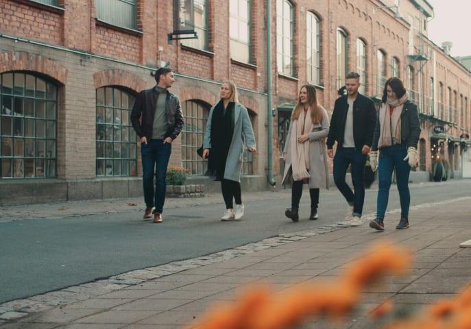 Två män och tre kvinnor går bredvid varandra på en gata.