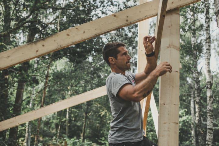 En man spikar fast en bräda i ett bygge. Mannen är fotograferad från sidan och är omgiven av fastspikade brädor och gröna träd. Mannen har på sig en grå t-shirt och svarta snickarbyxor.