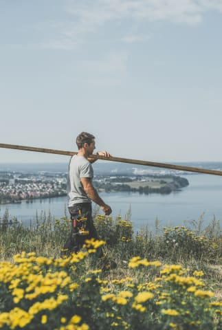 En man går med en bräda över axeln. Han är fotograferad från sidan. Framför mannen syns gula blommor, och bakom honom syns Huskvarna och vättern. Himlen och vattnet är ljust blå.