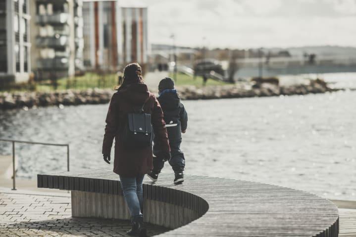 En kvinna och ett litet barn är fotograferade bakifrån medan de går tillsammans på Atollen. Pojken går på en bänk. Bredvid dem syns Munksjön. Det är höst och ljust ute.