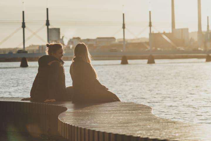 Två kvinnor sitter på en bänk intill Munksjön. De är fotograferade snett bakifrån och pratar med varandra. Solen håller på att gå ner. I bakgrunden syns Munksjöbron.