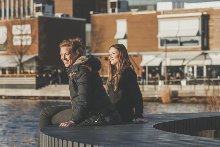 Två kvinnor sitter på en bänk intill Munksjön. De är fotograferade snett framifrån. De ler och skrattar och har solen i ansiktet. Bakom dem syns caféer och restauranger.