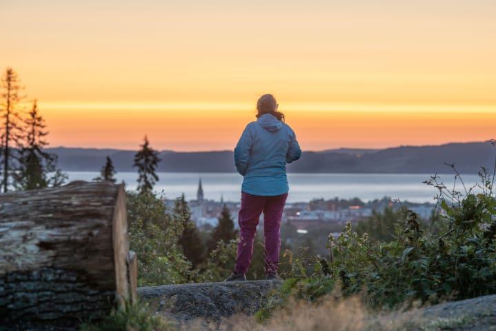 En kvinna är fotograferad bakifrån medan hon tittar på utsikten. Framför henne syns Jönköping och Vättern. Solen håller på att gå upp och himlen är orange.