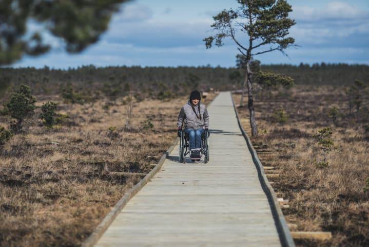 En ung rullstolsburen kvinna tar sig fram på Dumme mosse. Hon är fotograferad rakt framifrån och är den enda människan som syns i bilden. Bilden är tagen på hösten, solen skiner och himlen är blå.