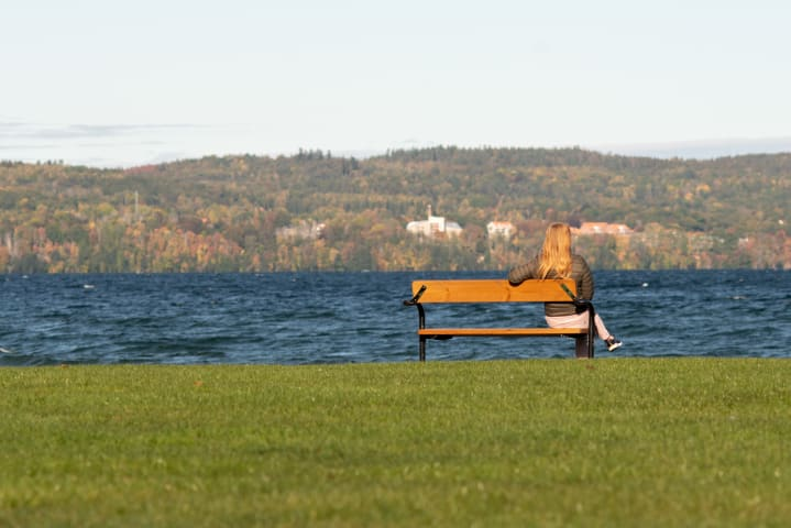 En kvinna sitter på en parkbänk på Vätterstranden och tittar ut mot vattnet. Hon är fotograferad bakifrån. Solen skiner och vattnet är mörkblått.