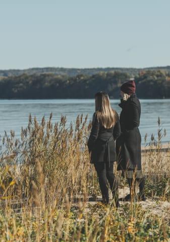 Två kvinnor står bredvid varandra och tittar ut mot Vättern. De är fotograferade snett bakifrån. Solen skiner och vattnet är ljusblått.