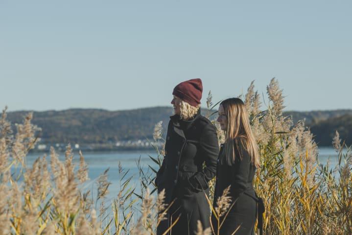 Två kvinnor står bredvid varandra och tittar ut mot Vättern. De är fotograferade från sidan. Solen skiner och vattnet är ljusblått.