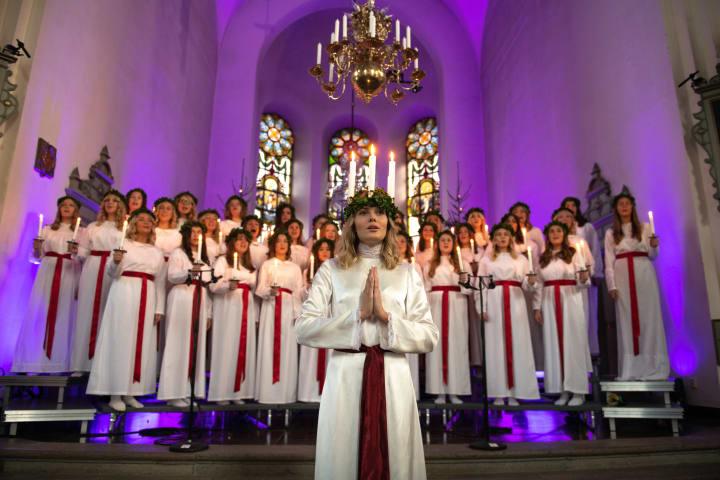 En kvinna i Luciadräkt står längst fram och sjunger. Bakom henne står en kör av tärnor. De befinner sig i en kyrka.