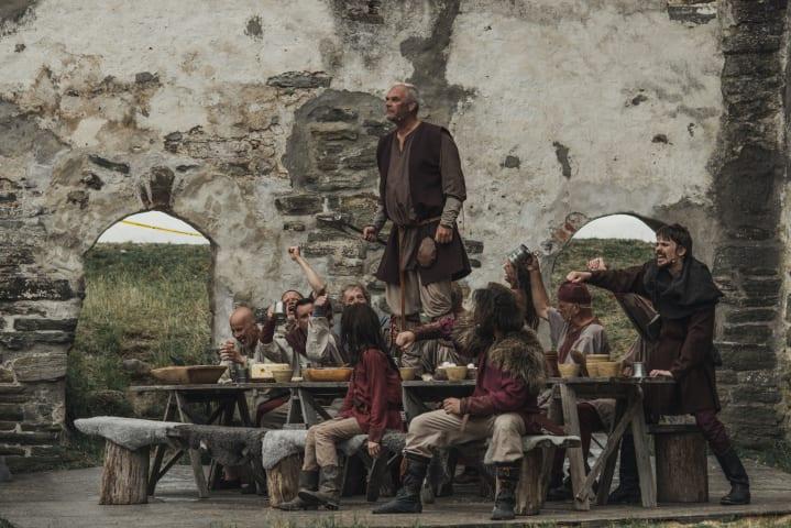 En scen från teaterföreställningen Ronja Rövardotter. Skådespelare är samlade runt ett bord.