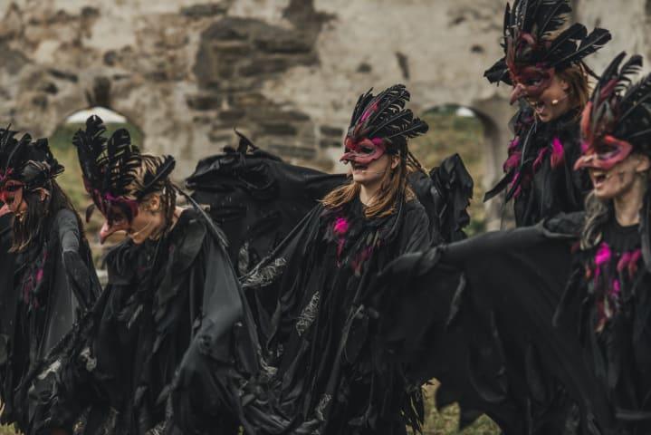 Barn är utklädda till vildvittror i teaterföreställningen Ronja Rövardotter. De har på sig svarta dräkter med lila detaljer.