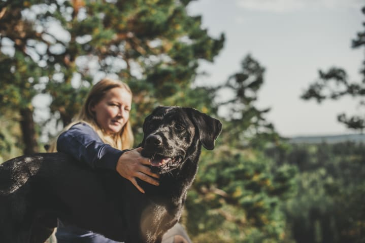 En kvinna håller sin ena arm omkring en hund. De är fotograferade från sidan och befinner sig i en skog.