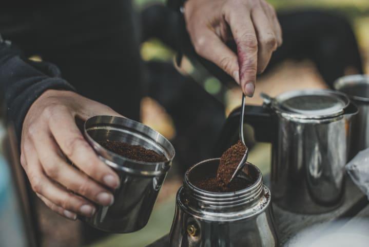 En person fyller upp malt kaffe i en burk. Bilden är tagen utomhus.