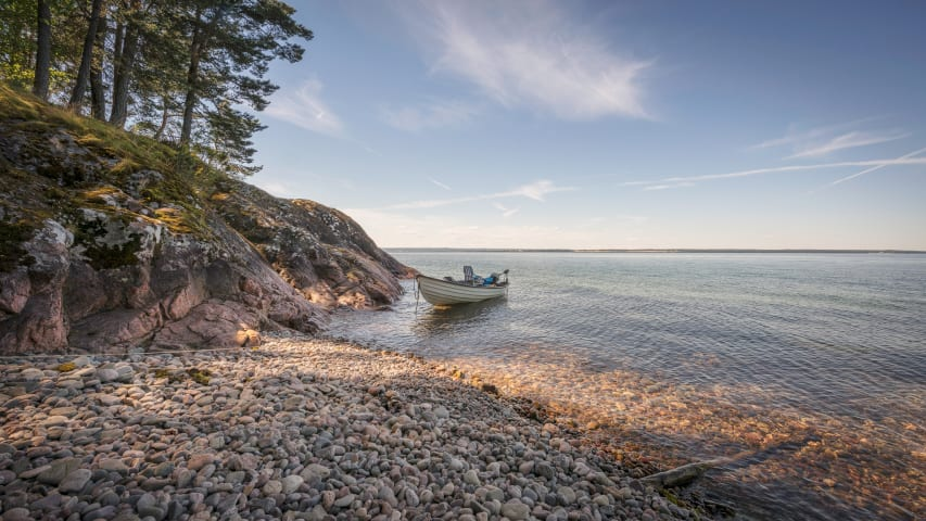 En båt ligger i vattnet nära strandkanten, som är full av småstenar. Vattnet är klart och ljusblått.