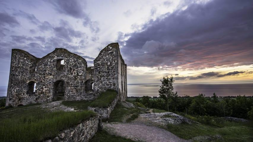 Brahehus är fotogaferat framifrån i skymningen. Bakom ruinen syns Vättern och en rosa himmel.