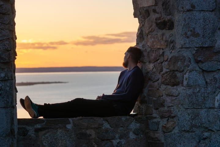 En man är fotograferad från sidan när han sitter i ett fönster i Brahehus ruin. Han tittar bort från kameran, ut mot utsikten över Vättern. Det är skymning och himlen är orange.