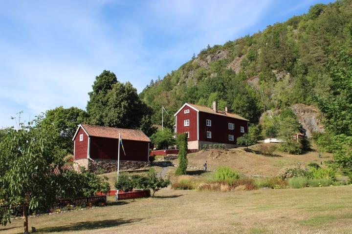 Två röda hus ligger i en sluttning. Det är sommar och himlen är blå.