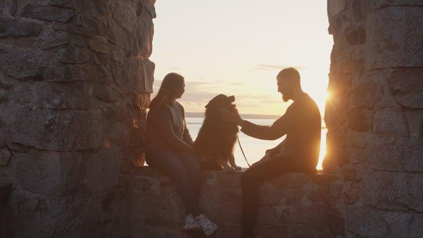 En kvinna och en man sitter i ett fönster i Brahehus ruin. Mellan dem sitter en hund. Mannen och hunden tittar på varandra, och kvinnan tittar ut på utsikten framför dem. Bakom människorna och hunden syns Vättern och solen som håller på att gå ner.