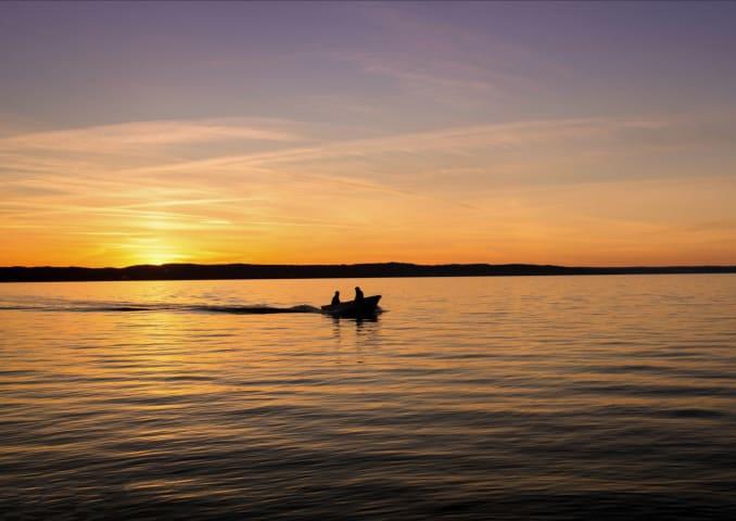 Två människor sitter i en båt mitt i en sjö. Solen håller på att gå upp och vattnet och himlen är mörkt blå och orange.