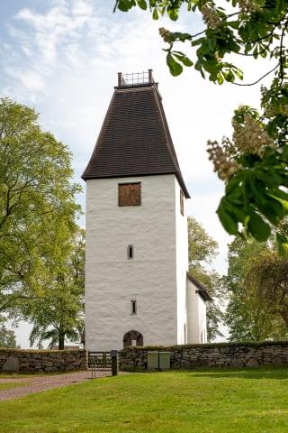 Kumlaby kyrka är fotograferad framifrån. Träd och en stenmur omger byggnaden.